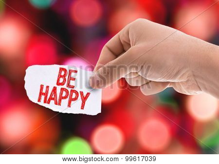 Piece of paper with the word Be Happy with bokeh background