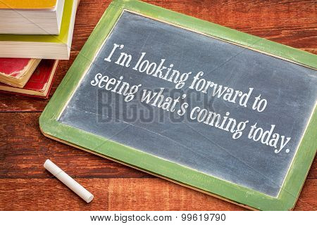 I am looking forward to seeing what is coming today - positive affirmation phrase on a slate blackboard with a white chalk and a stack of books against rustic wooden table