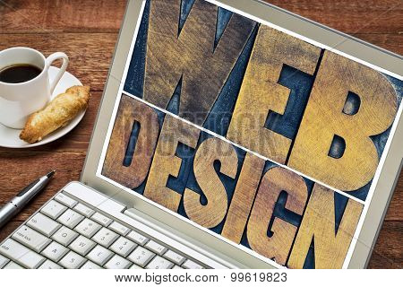 web design word abstract - text in vintage letterpress wood type block on a laptop screen with a cup of coffee