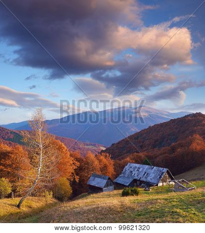 Wooden house in the mountain village. Autumn landscape. Sunny evening. Carpathians, Ukraine, Europe