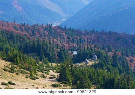 Mountain landscape with wooden church in the autumn forest. Carpathians, Ukraine, Europe
