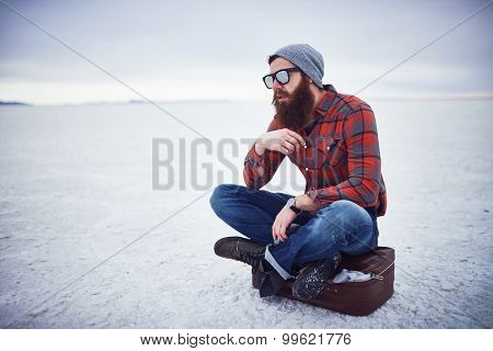 pensive contemplative hipster stroking awesome manly beard sitting on retro suitcase in salt flats all alone with copy space composition