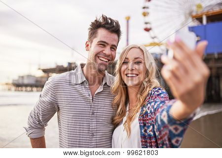 romantic couple taking selfie together on the beach in santa monica california