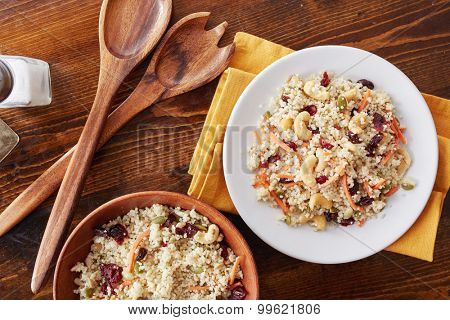 couscous cold salad with nuts, seeds, cranberries and carrots being served on a plate from bowl overhead photo