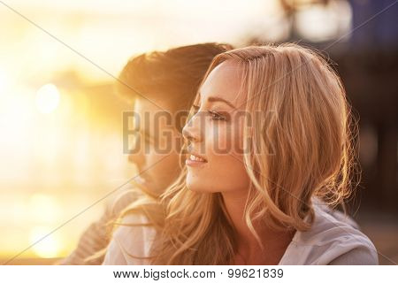 romantic couple cuddling on beach at sunset with lens flare