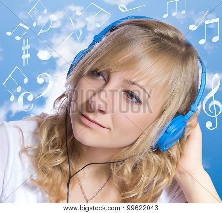 Attractive young woman listening to music on headphones.