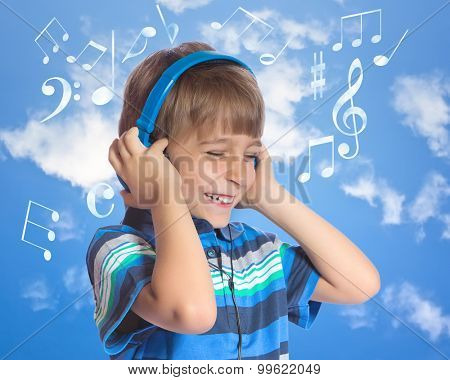 Attractive young boy listening to music on headphones.