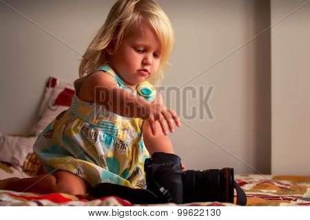 Little Blonde Girl Looks Into Camera On Sofa Against White Wall