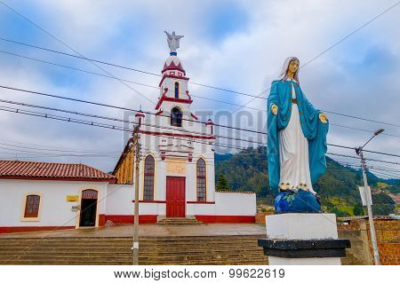 Virgin statue with blue cape guarding church building from historic city Zipaquira