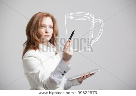 young woman with pen draws a Cup of coffee on grey background