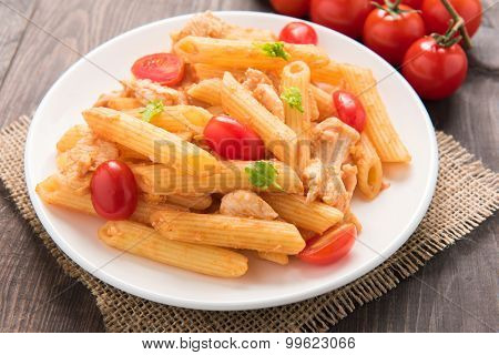 Penne Pasta In Tomato Sauce With Chicken On A Wooden Table