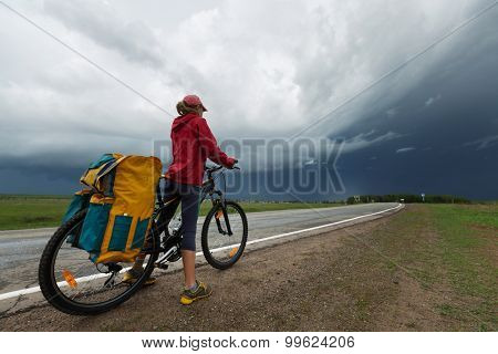 Hiker with bicycle standing on the paved road with storm clouds on the background