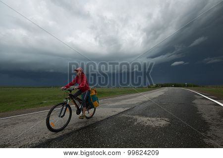 Lady cycling on the paved road with storm clouds on the background
