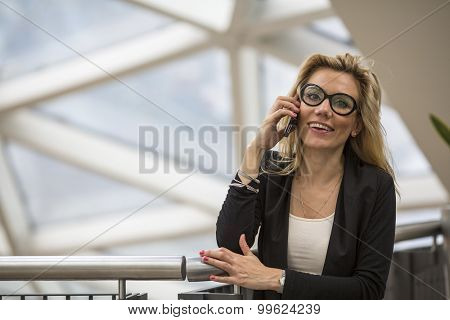 Attractive successful business woman speaks on a cell phone.