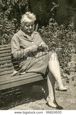 Vintage photo of woman knitting on bench, 1950's