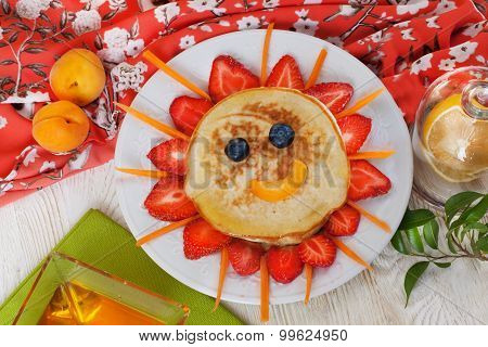 Children's breakfast pancakes smiling face of the sun strawberry blueberry and apricot, cute food, h