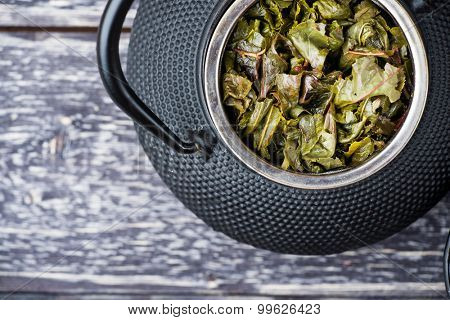 Top view of black iron teapot with green tea leaves on wooden background