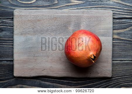 Red juicy pomegranate on dark rustic wooden background