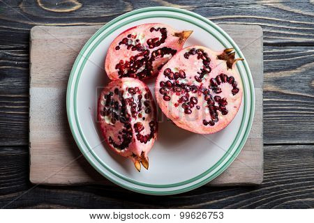 Red juicy pomegranate on the plate over dark rustic wooden background