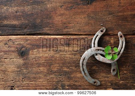 St. Patricks day, lucky charms. Two horseshoes with a four leaved clover on wooden board