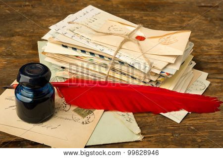 Red quill feather and ink well lying on an old table with nostalgic letters