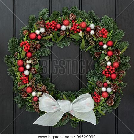 Christmas wreath with white bow, red and silver bauble decorations, holly, mistletoe, pine cones and blue spruce fir over dark oak background.