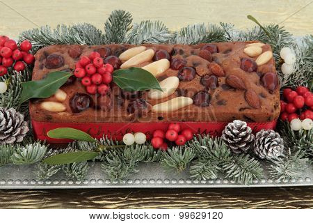 Genoa cake with holly, mistletoe and winter greenery on a silver plate over gold tablecloth background.