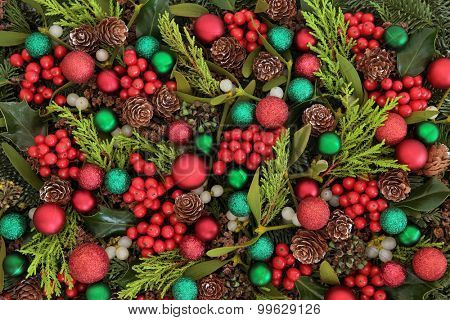 Christmas abstract background with red and green bauble decorations, holly, ivy, mistletoe, blue spruce fir and cedar cypress greenery.