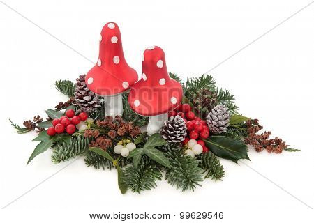 Christmas flora with fly agaric mushroom baubles, holly, mistletoe, ivy, pine cones and traditional greenery over white background.