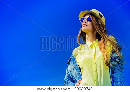 Beautiful happy girl wearing casual jeans clothes enjoys sunny summer day. Beauty, fashion shot.