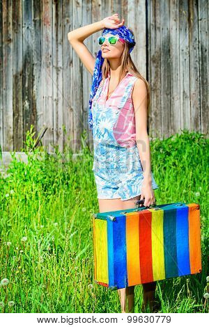 Young romantic girl with bright striped suitcase standing outdoor surrounded by lush green trees. Summer colors. Fashion shot.