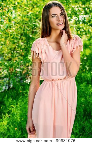 Beautiful smiling young woman in light summer dress standing outdoor next to a lush green trees. Summer style.