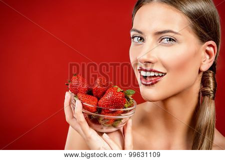 Joyful young woman eating fresh strawberry and smiling. Healthy food concept. Red background.