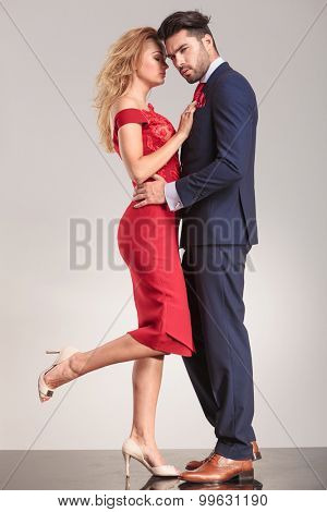 Elegant couple standing face to face embracing.