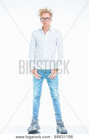 Full body picture of a young fashion man standing while holding his thumbs in pockets.