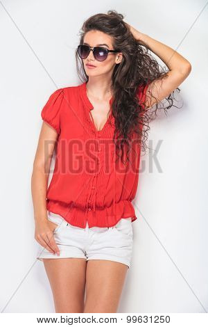 Gorgeous young woman fixing her hair while holding one thumb in her pocket.