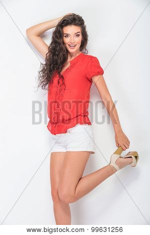 Happy young woman holding her shoe by the heel while smiling at the camera.
