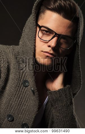 Portrait of a young fashion man holding one hand to his neck while looking at the camera.