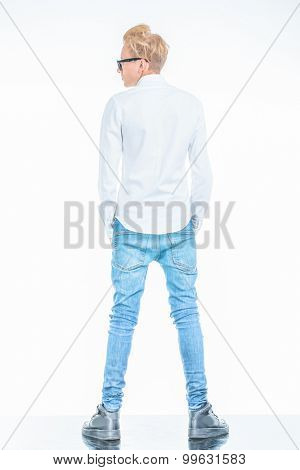 Rear view of a casual young man holding his hands in pockets while standing on studio background.