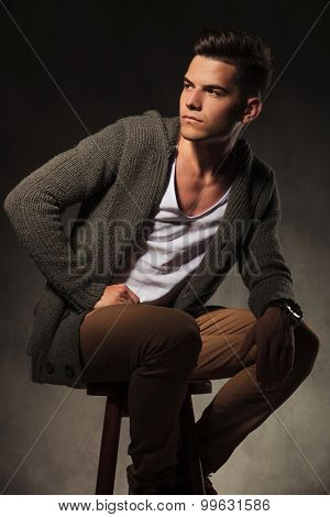 Attractive young man looking away from the camera while sitting on a chair.