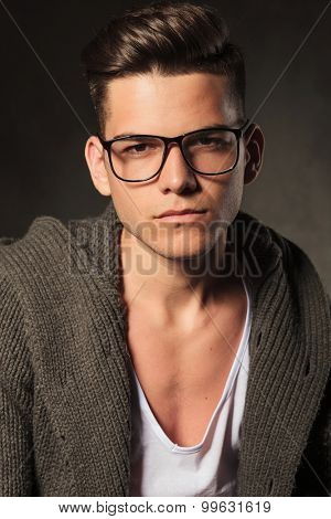 Portrait of a casual young man posing on grey studio background.