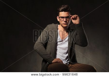 Handsome young man sitting while fixing his glasses.