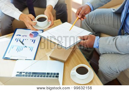 Businessmen reading and discussing contract