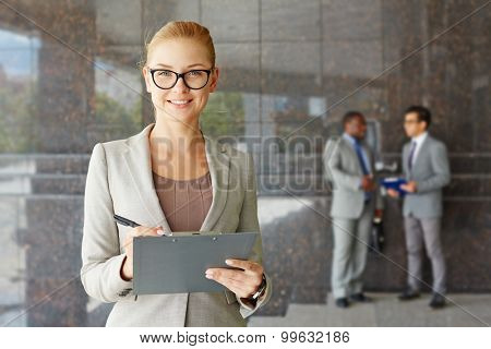 Young seriously looking businesswoman smiling at camera