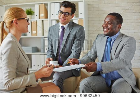Businessmen reaching out contract to a woman