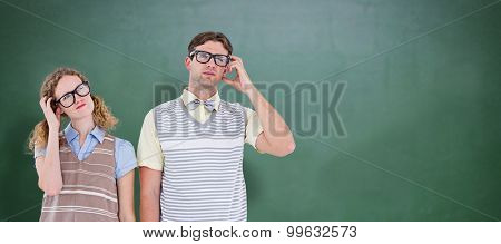 Geeky hipster couple thinking with hand on temple against green chalkboard