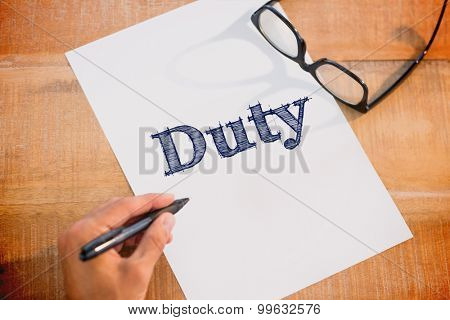 The word duty against left hand writing on white page on working desk