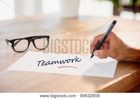 The word teamwork against side view of hand writing on white page on working desk