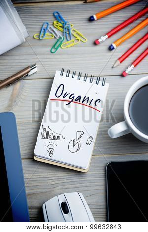 The word organic and business graphs against notepad on desk