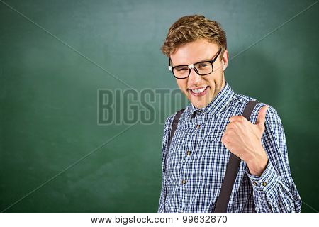 Geeky hipster showing thumbs up against green chalkboard